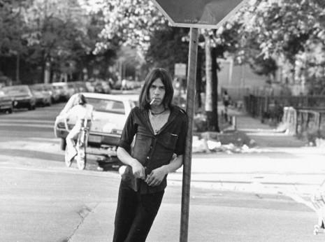 Photo of young man leaning against stop sign in Chicago