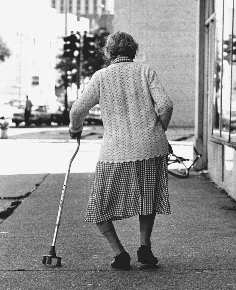Old woman with bow legs and cane in Uptown, Chicago during the mid-1970s.