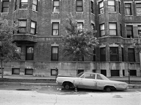 Automobile stripped and left on the street of Uptown in 1974.
