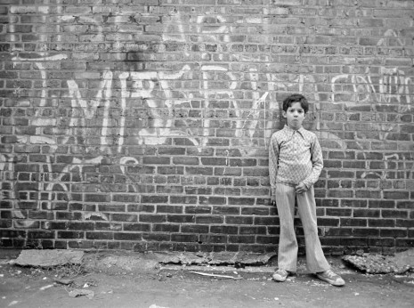Boy against a wall filled with graffiti in Chcago